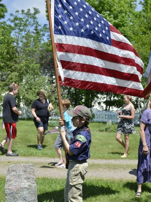 Noah Dreibelbis, 9, of Underhill, a Cub Scout with Pack 620, holds an American flag at the Pleasant View Cemetery in Jericho during the town's Memorial Day ceremony on Monday.