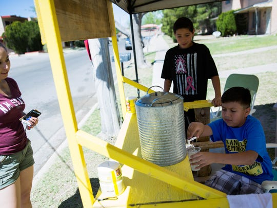 Angel Reyes,9,right, pours a glass of lemonade for Selinda Alvarez Garay at his Lemonade stand, where Reyes is using the money he earns to help with his grandfathers cancer treatment, Wednesday, March 22, 2017.