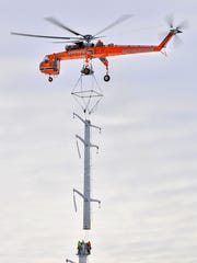 A helicopter from Erickson Air-Crane moves the top section of a 155-foot power transmission tower into position in 2011 in the Bel Clare marsh near Minnesota Highway 23 and Bel Clare Drive. XCel Energy officials on scene said the helicopter was used to set two towers into position in the marsh because ice in the marsh could not support other equipment to lift the 45,500 pound structure into position.
