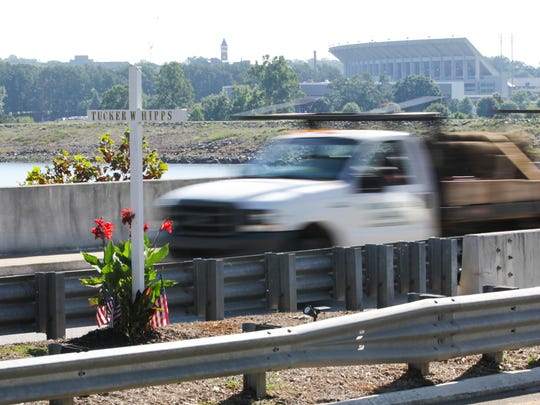 A truck drives past a cross standing in remembrance of Tucker Hipps on the S.C. 93 bridge Wednesday. Clemson's Memorial Stadium is in the background.