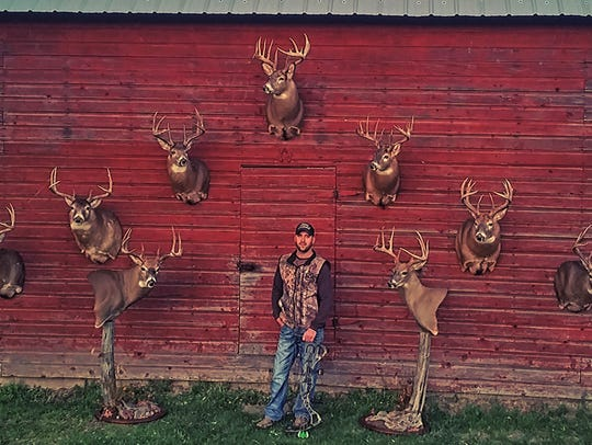 Aaron Knutson poses with nine white-tailed bucks –