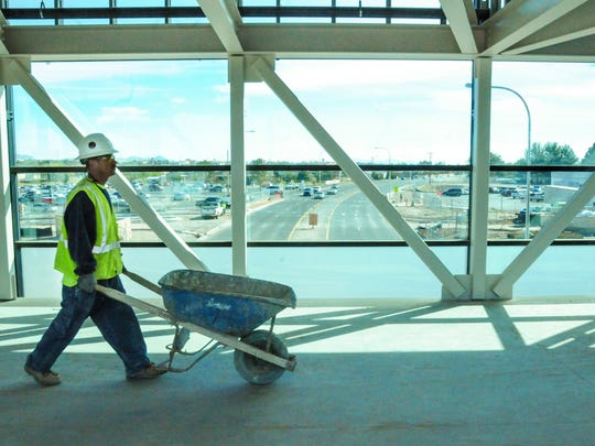 Wooten construction worker Tony Ortiz walks with a wheelbarrow in the Las Cruces High School sky bridge on Wednesday as phase one -- structural steel -- of the renovation project is completed.
