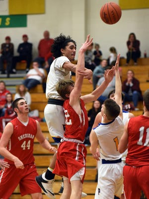 Philo's Isaac Gill blocks the shot of Landon Russell during the Electrics' 62-52 loss on Friday night at The Power Plant. It was Sheridan's eighth straight victory.