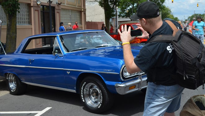 Brian Inferrera of Millville lines up a photograph of this 1964 Chevy Chevelle at the Millville Car Show.