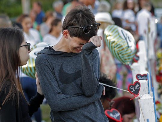Daniel Bishop, 16, a student at Marjory Stoneman Douglas High School, cries at a makeshift memorial outside the school, in Parkland, Fla., Sunday, Feb. 18, 2018. Nikolas Cruz, a 19-year-old who had been expelled from the school, is being held without bail in the Broward County Jail, accused of 17 counts of first-degree murder. (AP Photo/Gerald Herbert)