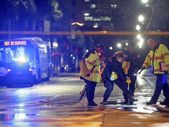 New Orleans Police crime scene technicians place evidence cones on Elk Place at Canal Street after police got into a shooting with an armed robbery suspect in New Orleans, La., Feb. 17, 2019.