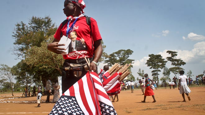 "A vendor selling flags, caps and T-shirts, and wearing a shirt showing President Barack Obama with words in Luo reading ""Father has reached home"", sells his wares at an event attended by Sarah Obama, the step-grandmother of the former president, in her hometown of Kogelo, Kenya, on July 18, 2015."