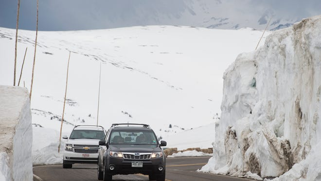 Cars navigate along tall snow drifts on Trail Ridge Road in Rocky Mountain National Park on Friday, June 2, 2017. The road, topping out at about 12,183 feet in elevation, opened for the season on May 31.