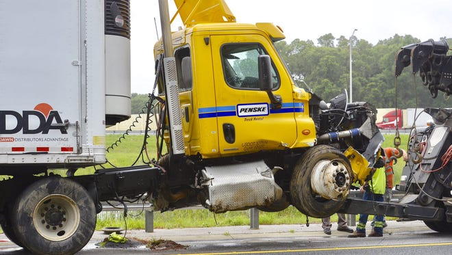 Workers clean up after an accident on the ramp from Interstate 110 North onto Interstate 10 West on Thursday, June 22, 2017.