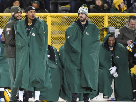 Injured Packers quarterback Aaron Rodgers, right, watches