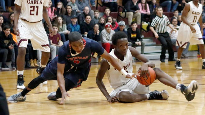 Stepinac's Jorden Means (0) left, and Iona Prep's Bryce Wilson (3) fight for a loose ball during basketball action at Iona Prep High School in New Rochelle on January 13, 2017.  Stepinac 58-52 win came after a suspension of the game due to a leak in the ceiling.