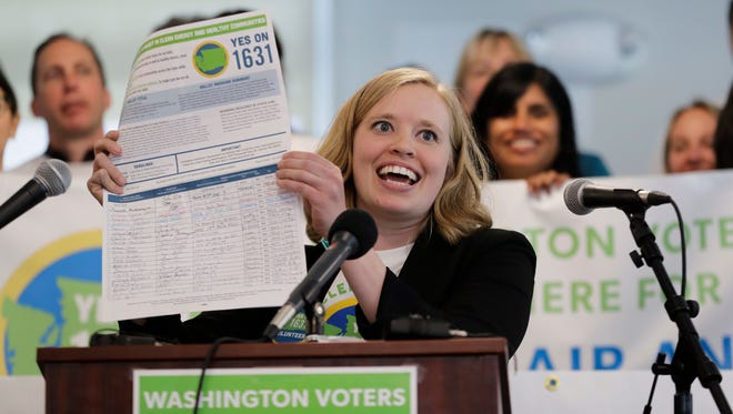Abigail Doerr, campaign director for Yes on 1631, holds up an initiative petition at a rally in Seattle in May. Washington state is trying once again to charge industrial emitters a fee for their carbon emissions.