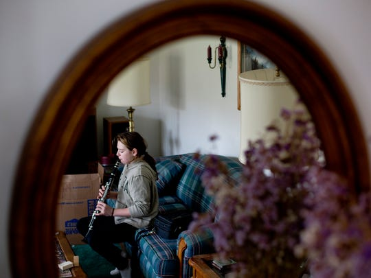 Jazmyne Simpson, 12, practices playing the clarinet on a couch in the lining room of their home in Fort Gratiot.