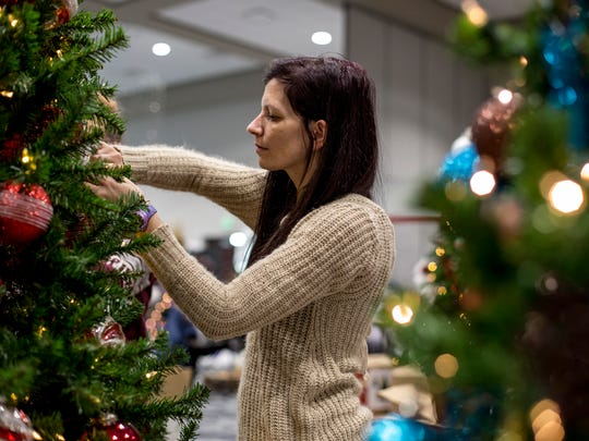 Lisa Yearkey, of Croswell, sets up a tree in preparation