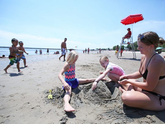 Maddy Speakman, 15, of Nyack makes a sand castle with her cousin Teagan Byrd, 7, center, and Mali Byrd, 9, who are visiting from Albuquerque, New Mexico, at Playland beach July 3, 2017 in Rye.
