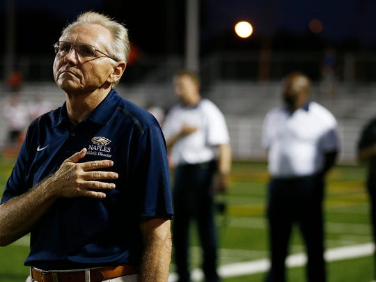Naples High School athletic director Ernie Modugno stands at attention during the national anthem on Oct. 9, 2015, before Naples' home game against Lely. (Daily News file)