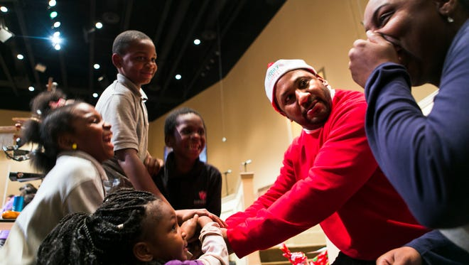 Zaniya Pirtle, 4 (bottom, from left); Keiara Pirtle, 9; Cortez Pirtle, 10; Cameran Kee, 5, and Sam Caviness II, look at Ashley Pirtle, 26, as Caviness gathers the group for a huddle before going to the stage to pick up a bag of Christmas gifts at First Baptist Church-Broad on Thursday evening. The church, the Memphis Police Department and the Rickey Smiley Foundation teamed up to give away toys and baskets of food to 105 needy families.
