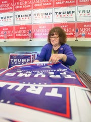 In prepartation for Donald Trump's Wednesday visit, Linda Pierce assembles lawn signs at the Trump campaign office in Pensacola on Tuesday, November 1, 2016.