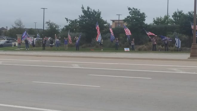 More than a dozen people gathered near the intersection of Preston Road and Prosper Trail in the late afternoon on Sept. 22 for what was dubbed the Trump and Back the Blue Rush Hour Rally. Participants - most wearing shirts, hats and other items in support of President Donald Trump as well as members of law enforcement - held flags and waved at passing vehicles as drivers honked.