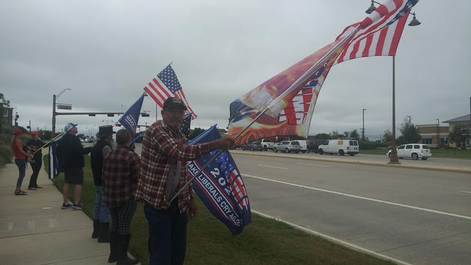 Bob Phillips holds a flag pole during a Sept. 22 rally on Preston Road. The Marine Corps veteran, who served during the Vietnam War, is a Prosper resident.