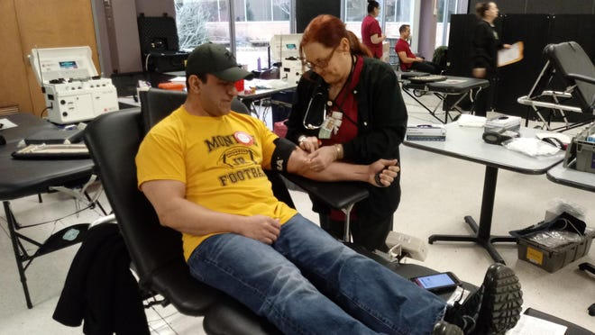Joy Wright, a registered nurse who works for the American Red Cross, preps the arm of Jack Pizzo of Monroe during a January blood drive at Monroe County Community College.