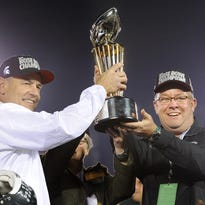 MSU football coach Mark Dantonio and athletic director Mark Hollis hold the Rose Bowl Championship trophy Jan. 1. Both are taking a wait-and-see approach to the new college football playoffs.