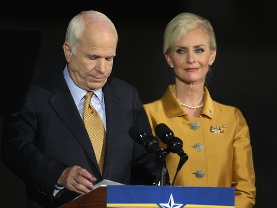 John McCain, on stage with his wife Cindy McCain, concedes