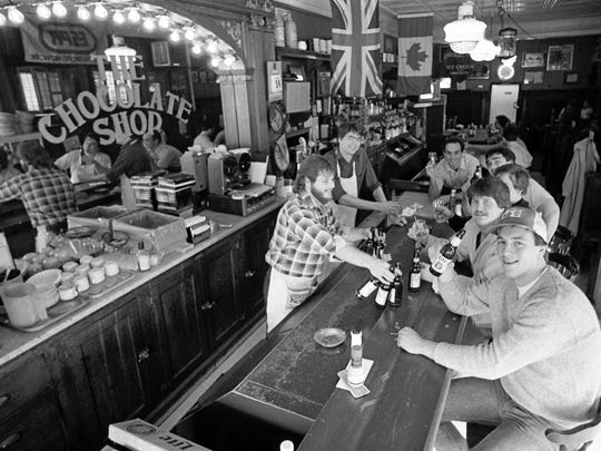 """The Chocolate Shop crew gathers for suds at the bar, which is becoming an institution for students and 'townies."""" Photo taken February 16, 1983."""
