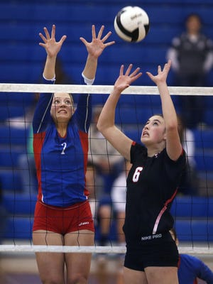 Roncalli's Bailey Schnel (left) defends the net against Center Grove's Taylor Hammill. Schnell finished with 16 kills.