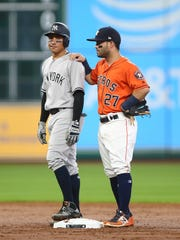 Houston Astros second baseman Jose Altuve (27) talks with New York Yankees second baseman Ronald Torreyes (74) during the second inning at Minute Maid Park on Friday, June 30, 2017.