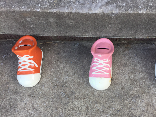 Three children's banks shaped like shoes sit on the front step of the home in Eastpointe where two young boys and a girl were killed in a house fire Saturday.