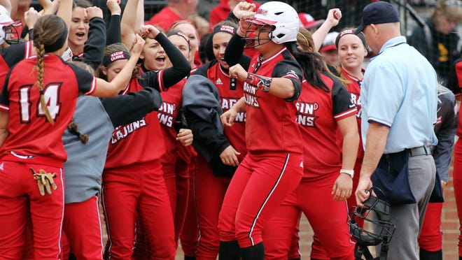 UL players celebrate as Samantha Walsh arrives after hitting a solo home run against Iowa in a game at Lamson Park on Friday. UL won 4-3.