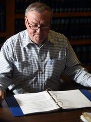 Ron Kincade looks over a guide of Statutory Duties,