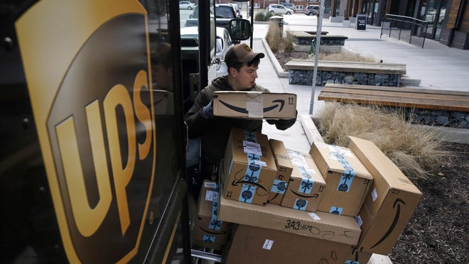 In this Dec. 19, 2018, file photo a UPS driver prepares to deliver packages. United Parcel Service Inc. reports earns on Thursday, April 25, 2019.