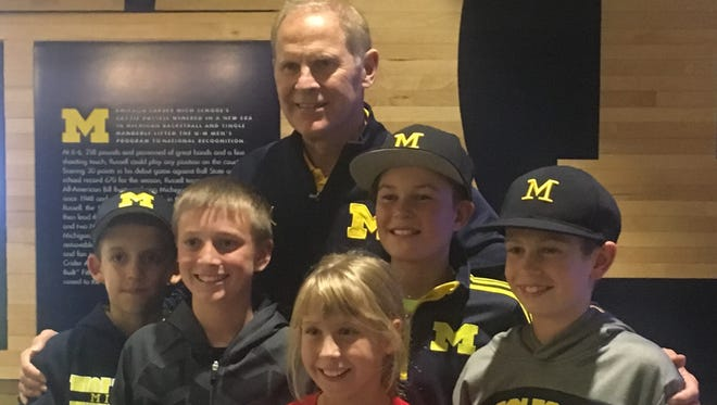 Michigan coach John Beilein, here taking a photo with a pack of young Wolverine fans following Tuesday's open practice at Crisler Center, was surprised by former player Trey Burke's complaints about food served to Wolverines.