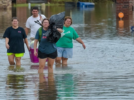 People wade in water near flood damaged homes in Highland