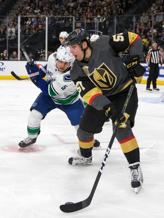 Vegas Golden Knights left wing David Perron (57) controls the puck as Vancouver Canucks defenseman Derrick Pouliot (5) over in during the second period of an NHL hockey game Tuesday, March 20, 2018, in Las Vegas. (AP Photo/L.E. Baskow)