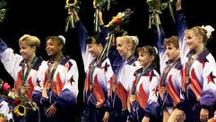 In a file photo from 1996, Team USA gymnasts wave after