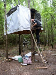 Investigator Ben Cothran of the Anderson County Sheriff's Office gets down from a homemade tree house in Anderson on Monday. Cothran, a code enforcement investigator, visits areas where people, many times homeless, set up a place to stay on property that is not theirs.