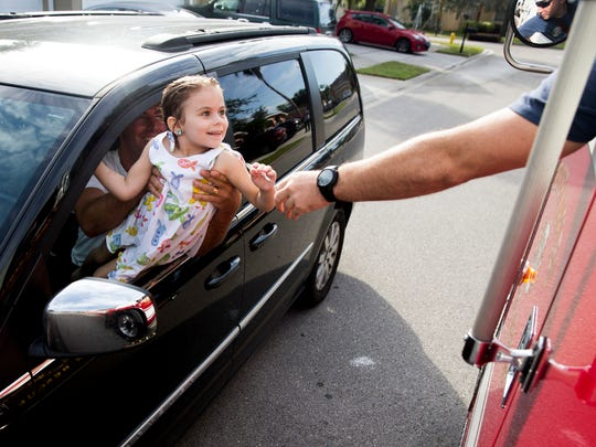 Driver Engineer John Richard, a firefighter with Greater Naples Fire Rescue Station 73, hands a little girl a candy cane as the engine passes by Sunday, Dec. 24, 2017, in North Naples.
