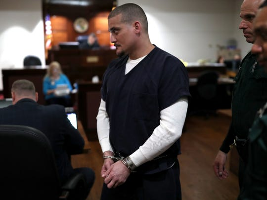 Accused murder suspect Sigfredo Garcia, being held