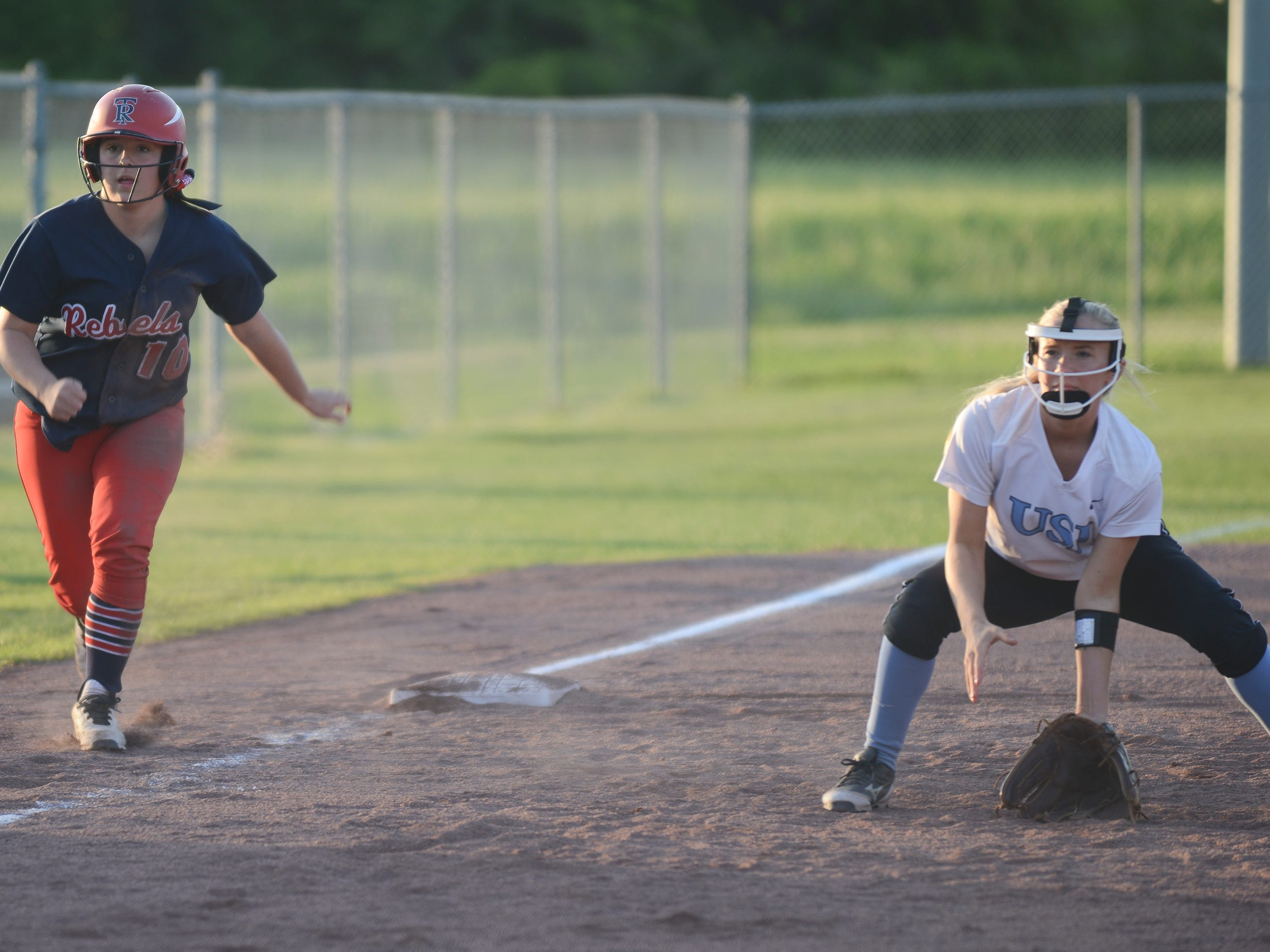 USJ's Molly Dowland gets ready to scoop a groundball with a Tipton-Rosemark player on third base.