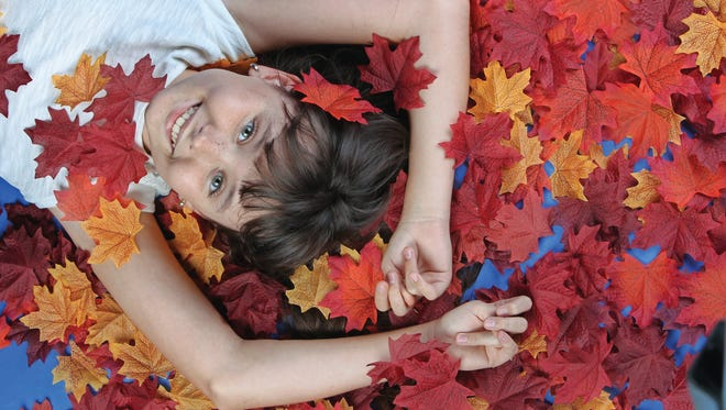 Sophie Huntington, 10, of Naples, lies in faux leaves for the SWFL Parent & Child cover shoot. The feature on fall events for families originally ran in the October issue of the magazine.