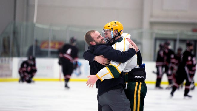 A D.C. Everest player celebrates with a coach after winning the boys hockey sectional final game between Stevens Point Area Senior High and D.C. Everest at the Greenheck Field House in Schofield, Wis., February 24, 2018.