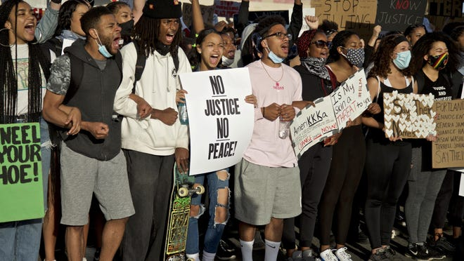 Demonstrators hold signs and shout in Portland during a protest over the death of George Floyd, who died May 25 after being restrained by police in Minneapolis.