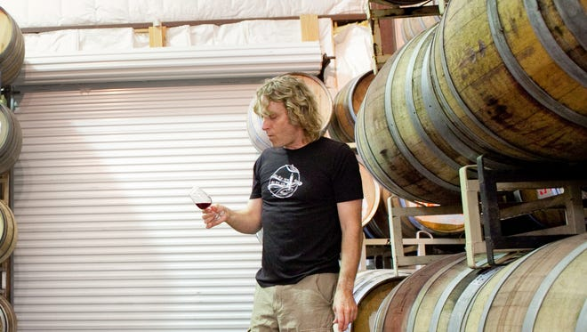 Eric Glomski tastes wine in the aging room at Page Springs Vineyards and Cellars in Cornville in October 2011.