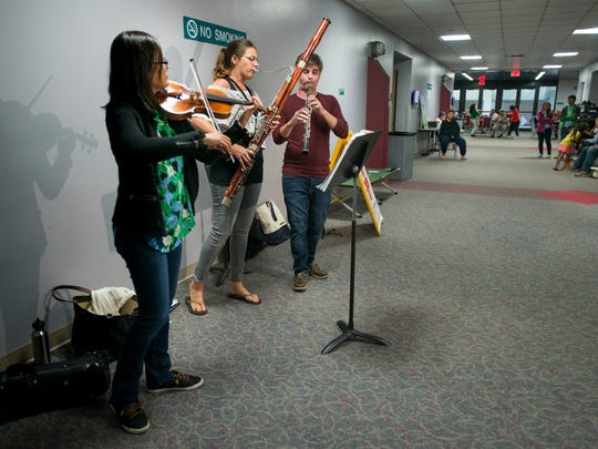 Violinist Grace Kim, bassoonist Abigail Walker, and oboist Asher Kelly, of the Pensacola Symphony Orchestra perform for evacuees at the Bay Center shelter in Pensacola, Florida on Monday, September 11, 2017.
