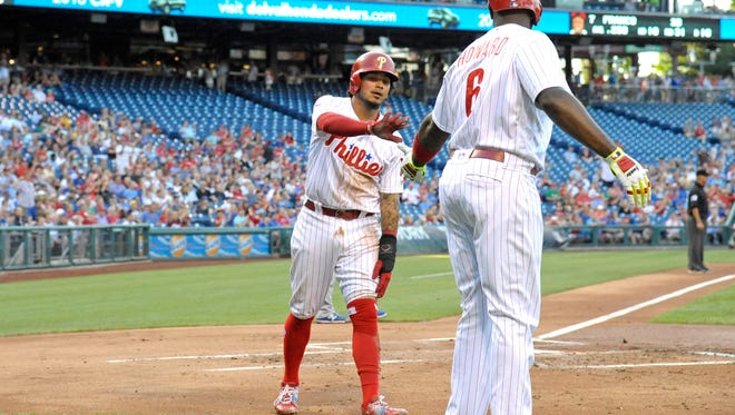 Phillies shortstop Freddy Galvis celebrates with first baseman Ryan Howard (6) after scoring a run during the first inning Tuesday against the Chicago Cubs.