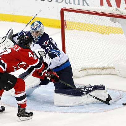 New Jersey Devils center John Quenneville (42) is unable