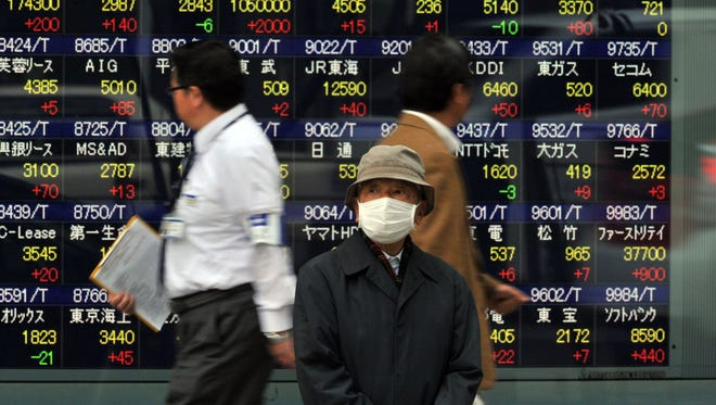 Pedestrians pass before a share prices board in Tokyo on Nov. 25, 2013.